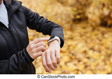 Close up of a sportswoman using smartwatch