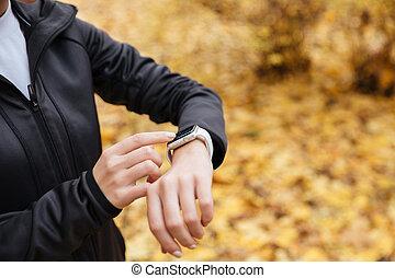 Close up of a sportswoman using smartwatch