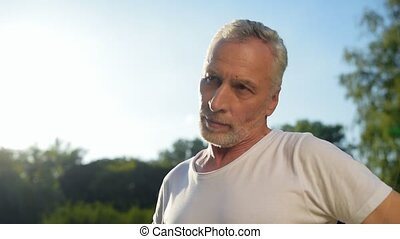 Close up of a sporty aged man doing warm up exercises