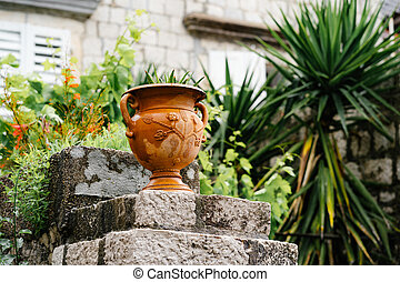 Close-up of a street flowerpot on the steps against the backdrop of a brick wall and greenery in the yard.
