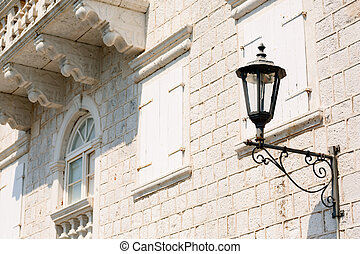 Close-up of a street lamp on the wall of a house under a balcony on a sunny day.