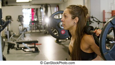 Close-up of a strong woman doing squats workout with heavy...