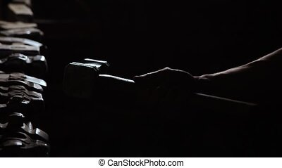Close-up of a sturdy man's hand takes a metal hammer on a dark background in slow motion. Smith takes his hand hammer for working with metal.