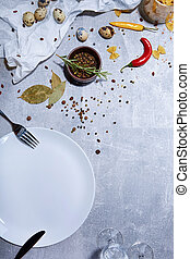 Close-up of a tableware next to a wooden bowl of seasoning. Quail eggs and bright chili peppers on a gray background.