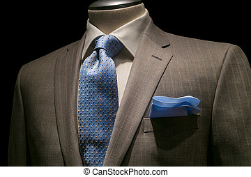 Close-up of a tan striped jacket with textured white shirt, patterned blue tie and blue handkerchief on black background. Clipping path included.