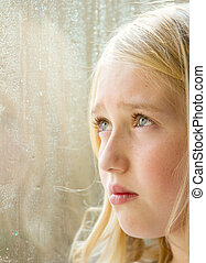 Close-up of a teen looking out a window