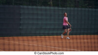 Close up of a tennis court grid in the background a woman is hitting a ball