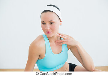 Close-up of a thoughtful woman in fitness studio