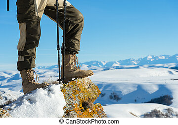 Close-up of a tourist's foot in trekking boots with sticks for Nordic walking standing on a rock stone in the mountains