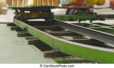 Close up of a train carnival ride on metal tracks in slow motion