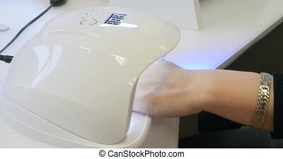 Close up of a uv led lamp with a female hand inside fixing the gel nail polish.