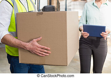 Close up of a warehouse worker carrying box