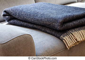 Close-up of a warm, navy blue, wool blanket with beige fringe on a comfy, gray sofa in a cozy living room interior