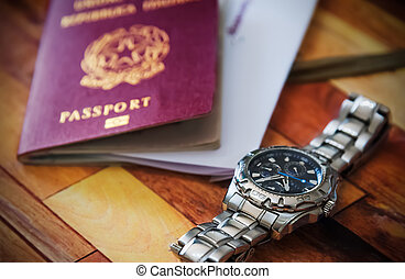 Close up of a watch with a passport on the background