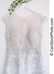 Close-up of a white corset of a bridesmaid dress with patterns on a hanger on a white background.