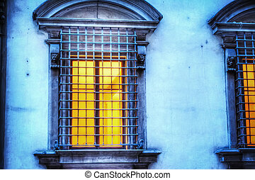 window with metal grill at night