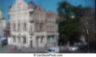 Close up of a window with rain drops. Blurry background -...