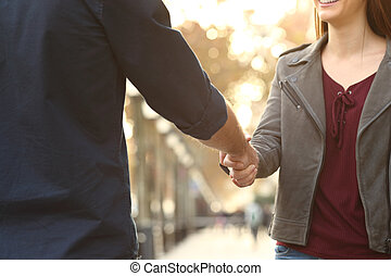 Close up of a woman and man handshking in the street