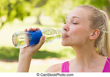 Close-up of a woman drinking water in park