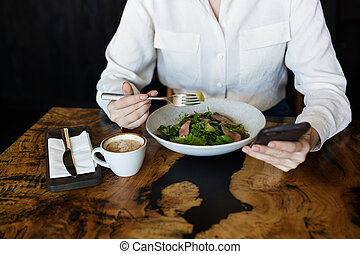 Close up of a woman eating salad while sitting at the cafe