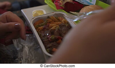 Close-up of a woman eats a lunch from a plastic container on the plane.