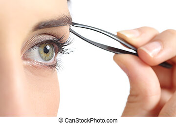 Close up of a woman eye and a hand plucking eyebrows isolated on a white background
