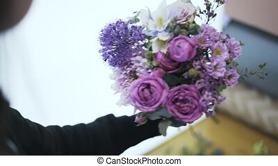 Close up of a woman florist arranging a bouquet of purple, white, pink flowers