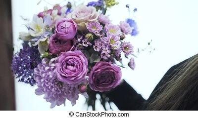 Close up of a woman florist holding a bouquet of beautiful flowers