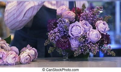 Close up of a woman florist making a purple bunch of flowers, pan shot