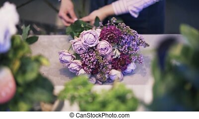 Close up of a woman florist making a purple bunch of flowers, tilt up