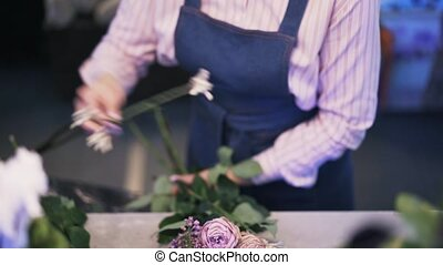 Close up of a woman florist making a purple flower bouquet, tilt down