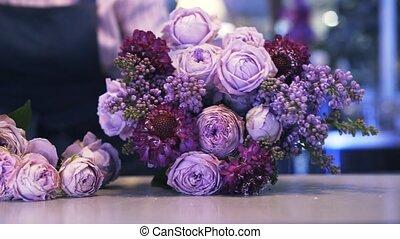 Close up of a woman florist making a purple bouquet, pan shot