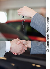 Close up of a woman giving car keys to a man