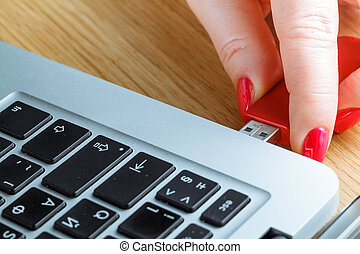 Close up of a woman hand plugging a pendrive on a laptop