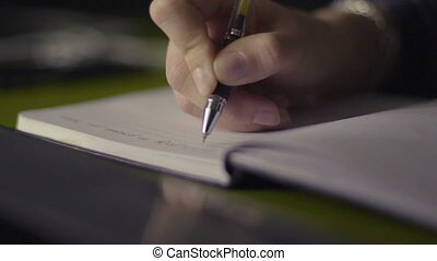 Close up of a woman hand writing in an agenda on a desk at...