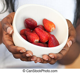 Close-up of a woman holding a bowl of strawberries