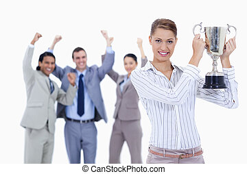 Close-up of a woman holding a cup with people dressed in suits acclaiming while watching her against white background