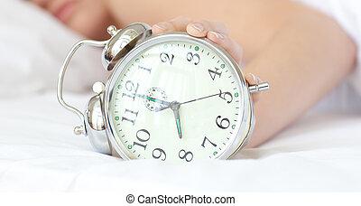 Close-up of a woman holding an alarm clock