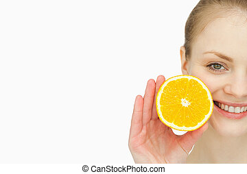Close up of a woman holding an orange in her hand
