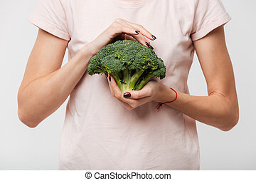 Close up of a woman holding broccoli