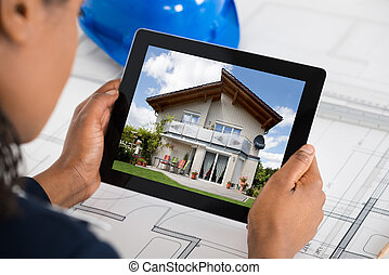 Woman Holding Digital Tablet Over Blueprint
