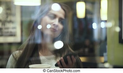 Close up of a woman in cafe on the phone