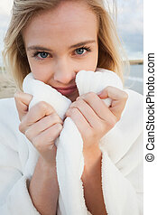 Close up of a woman in stylish white jacket on beach