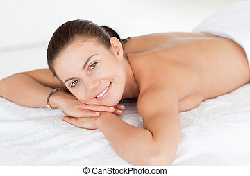 Close up of a woman lying on a massage table looking at the camera in a spa