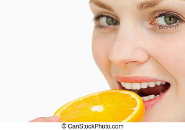 Close up of a woman placing a slice of an orange in her mouth