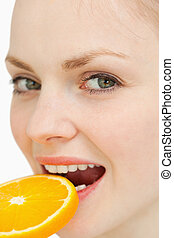 Close up of a woman placing a slice of orange in her mouth