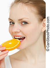Close up of a woman placing an orange slice in her mouth...