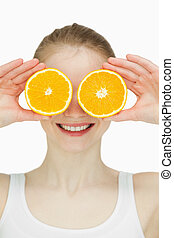 Close up of a woman placing oranges on her eyes against...