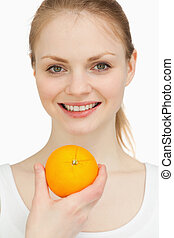 Close up of a woman presenting an orange while smiling