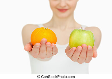 Close up of a woman presenting fruits